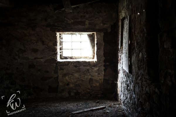 Stone walls of an empty barn illuminated by a spider webbed window.