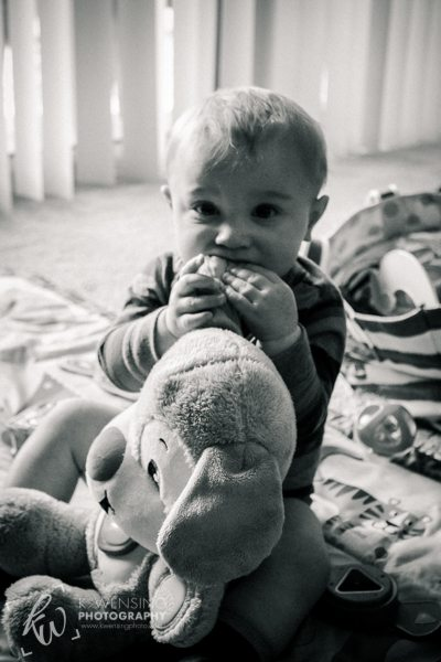 Black and white photo of baby and his stuffed animal.