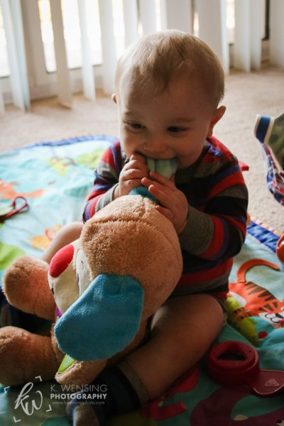 Smiling baby, chewing on stuffed puppy's ear.