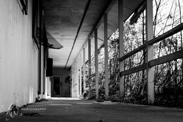 Black and white photo of abandoned motel walkway.