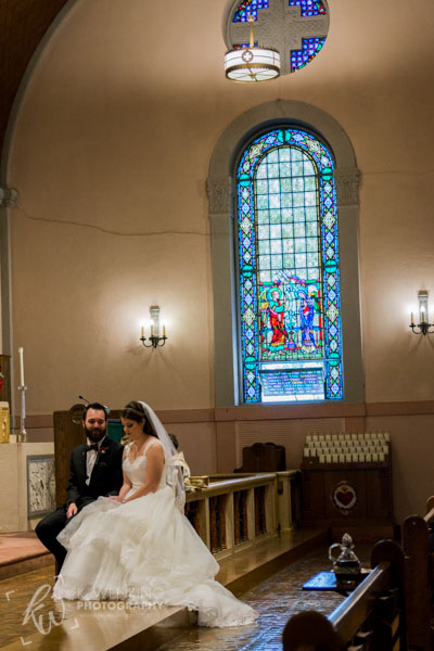 Bride and groom sitting patiently in church.