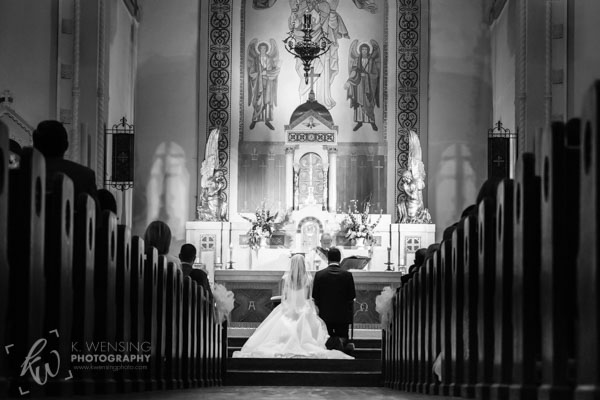 Beautiful black and white of a kneeling bride and groom in church.