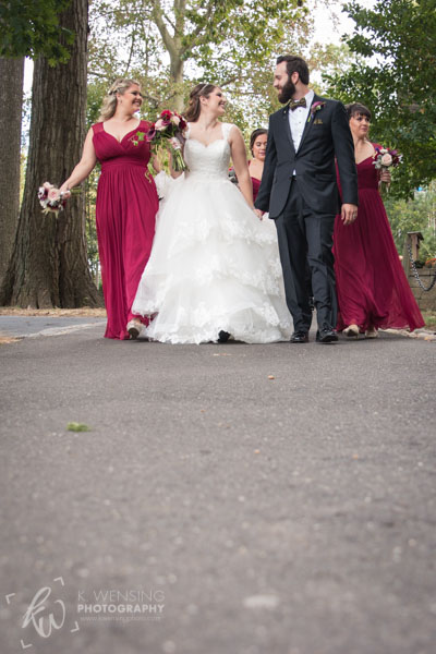 Groom with his bride walking with bridesmaids.