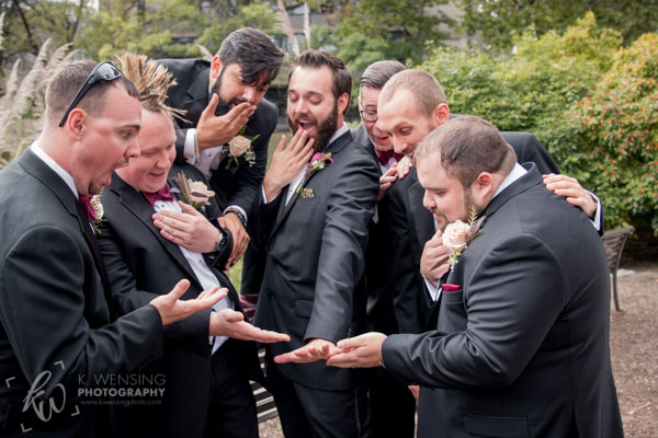 Groomsmen gawk over the groom's shiny, new ring.
