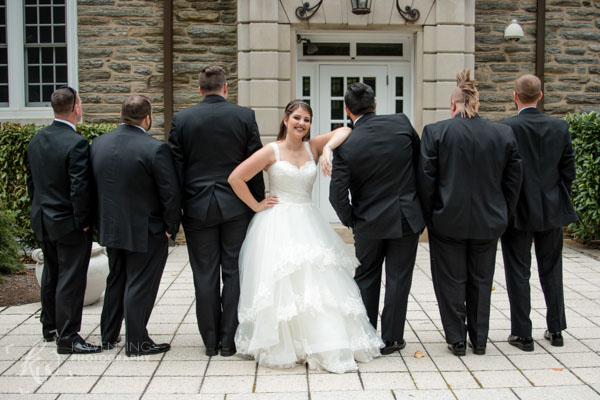 Bride poses with the groomsmen.