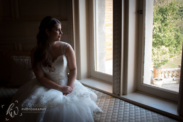 Bride sitting by window.