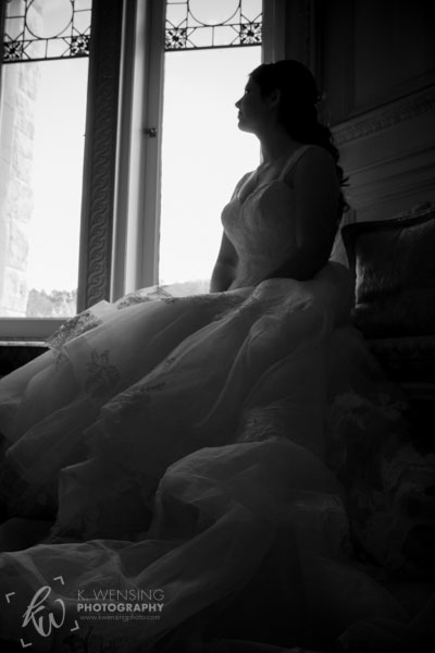 Black and white photo of bride seated by a window.