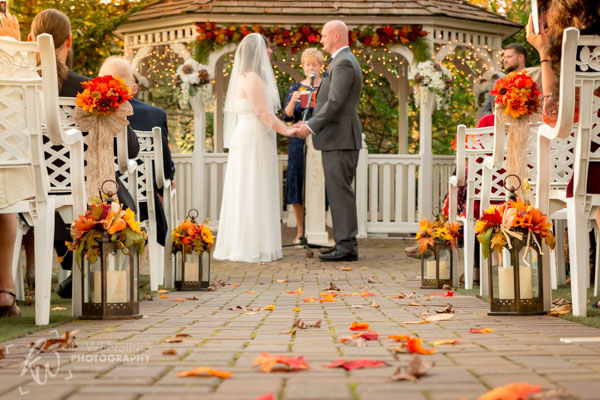 Aisle littered with Fall leaves during wedding ceremony.