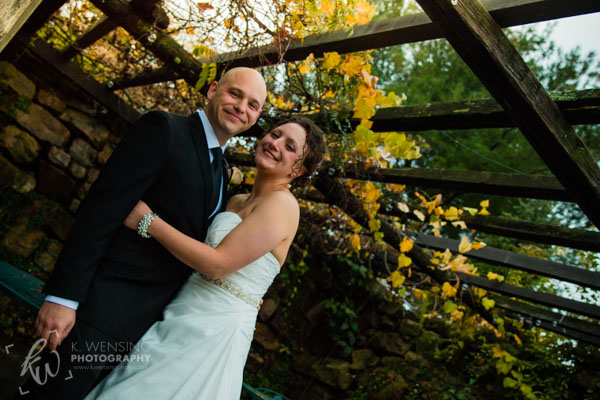 Newlyweds pose under the Autumn leaves.