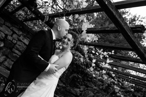Black and white photo of groom kissing his bride.
