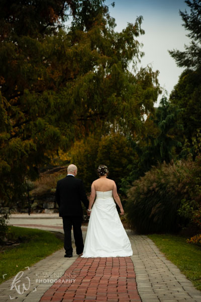 Newlyweds strolling along a path.