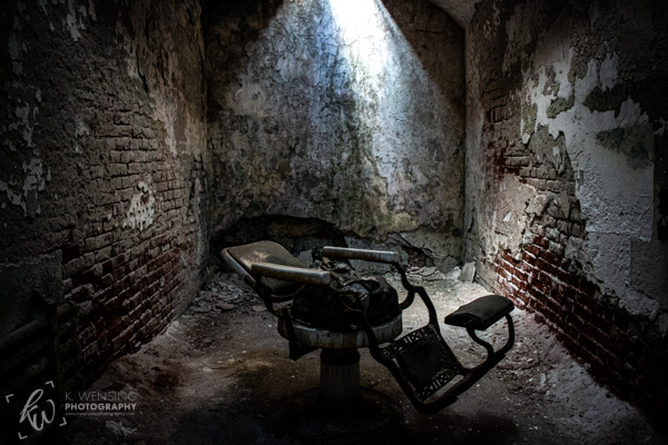 A chair resting in an old cell within the penitentiary.