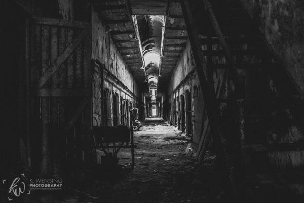 Black and white photo of an old penitentiary cell block.