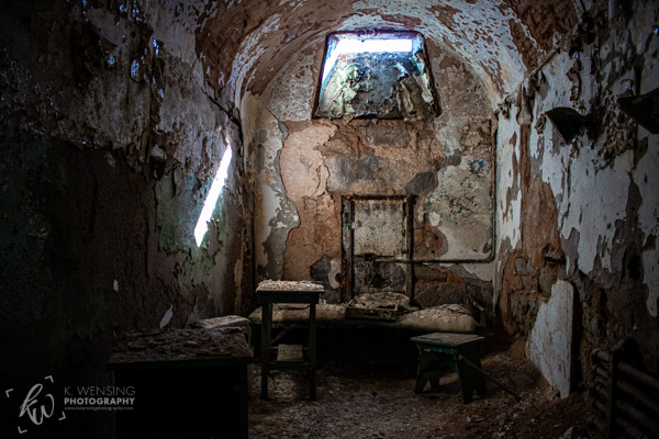 A cell with peeling paint on the walls of the Eastern State Penitentiary.