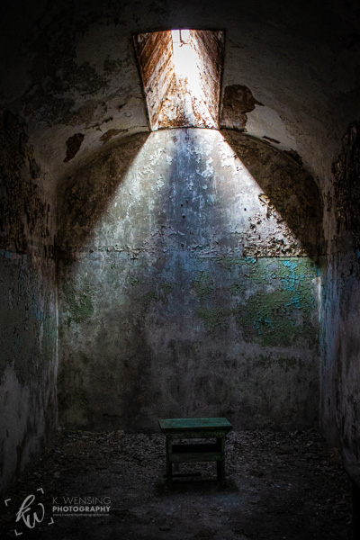 Light shining down on a stool in an Eastern State Penitentiary cell.