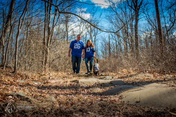 Couple wearing jerseys walk their dog in the woods.