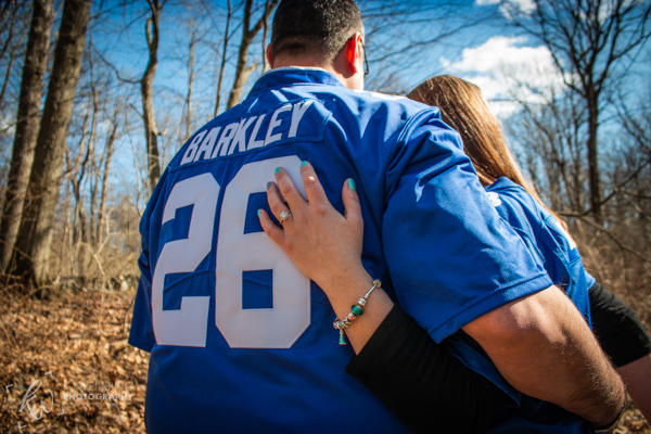 Engaged couple posing in their jerseys.