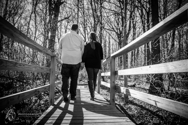 Black and white photo of engaged couple walking on a bridge in the woods.