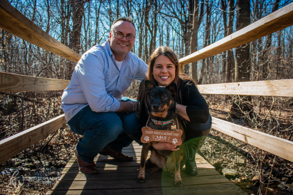 Newly-engaged couple posing with their dog.