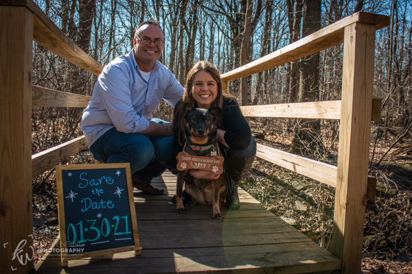 Couple and their dog, Bella, posting for an engagement photo together.