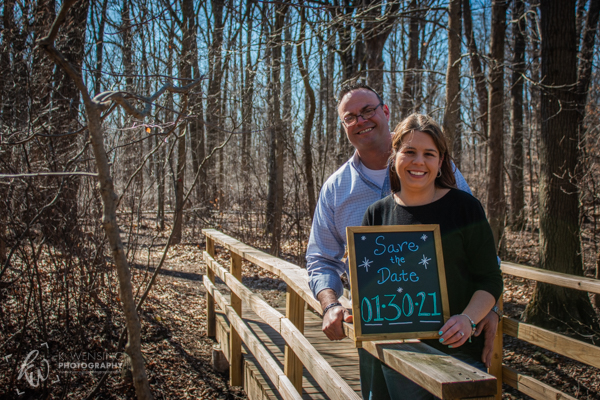 Couple posing with their save-the-date sign on the bridge.