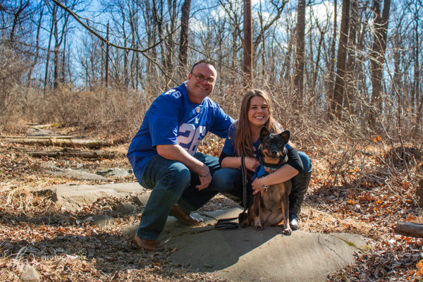 Engaged couple pose with their dog on a wooded trail.