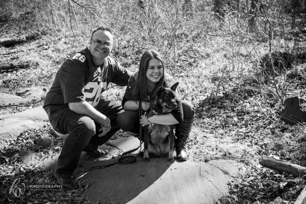 Black and white posing photo of engaged couple and their dog.