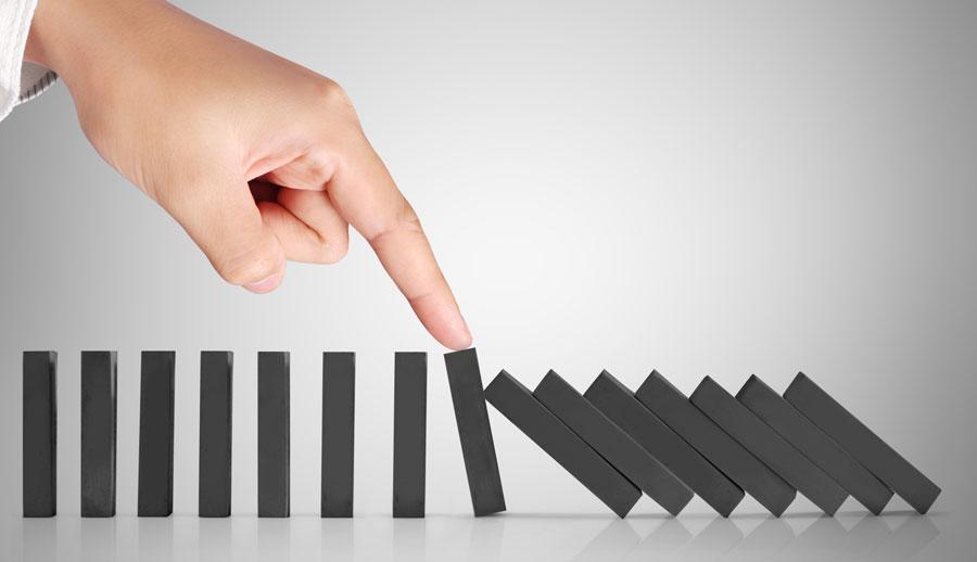 Mano sosteniendo pieza de domino como resolución de conflictos