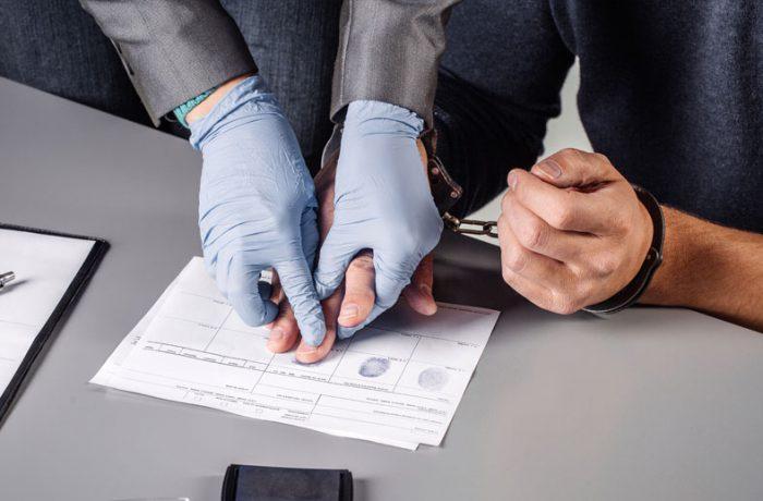 Gloves hands taking prints for criminal and transit