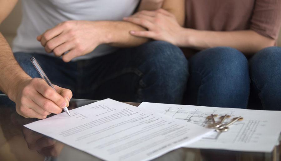 Pareja firmando un contrato por derecho de familia