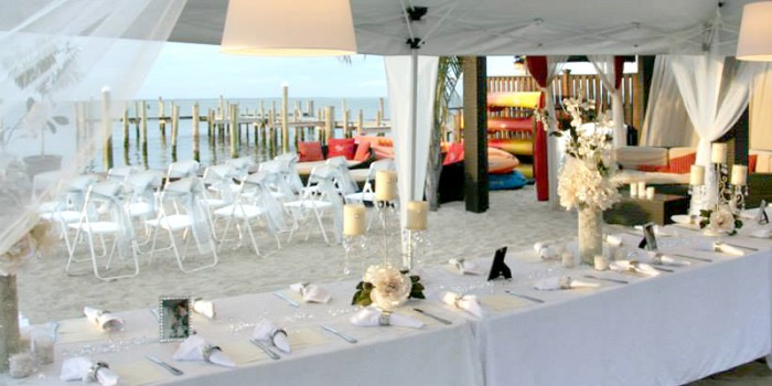 wedding dining table set up on the beach under a canopy
