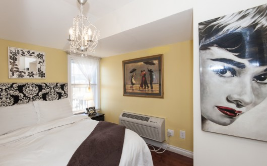 Room with Full size bed and painting of audrey hepburn on the wall