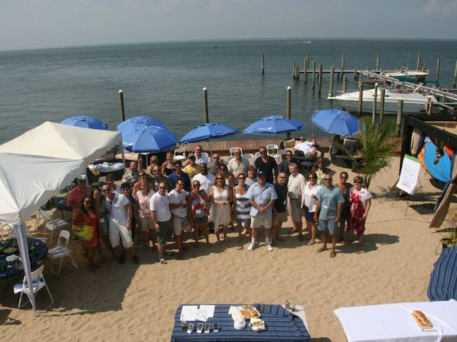 staff meating on the beach with seating under umbrellas and food served