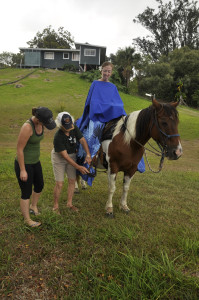 Tiare on horseback, while Barbara Nobriga demonstrates the proper placement of the pa'u around the foot.