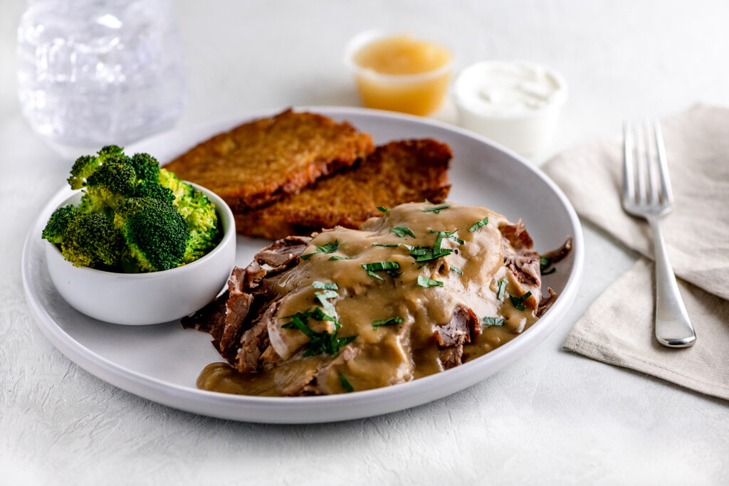 Beef brisket with brown gravy, side of broccoli and latkes with sour cream and apple sauce on a white plate.