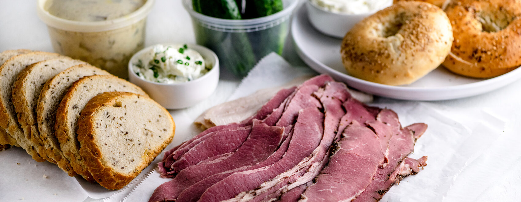 Sliced deli pastrami, corned beef and roast turkey beside a loaf of sliced rye bread, potato salad, NY bagels, cream cheese and pickles