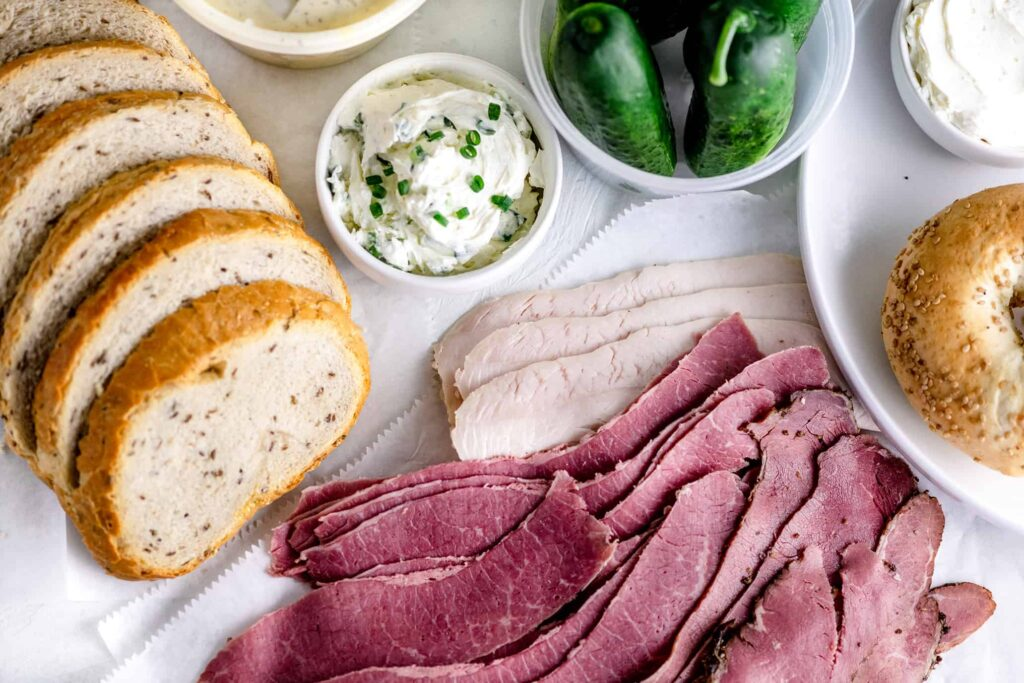 Slices of Bulk Corned Beef, Rye Bread, Turkey, New York Bagels, Cream cheese and Pickles