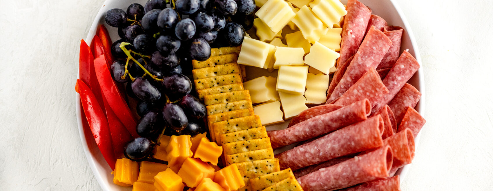 charcuterie board of rolled up meats, cheese bites, crackers, grapes and veggies on a white plate