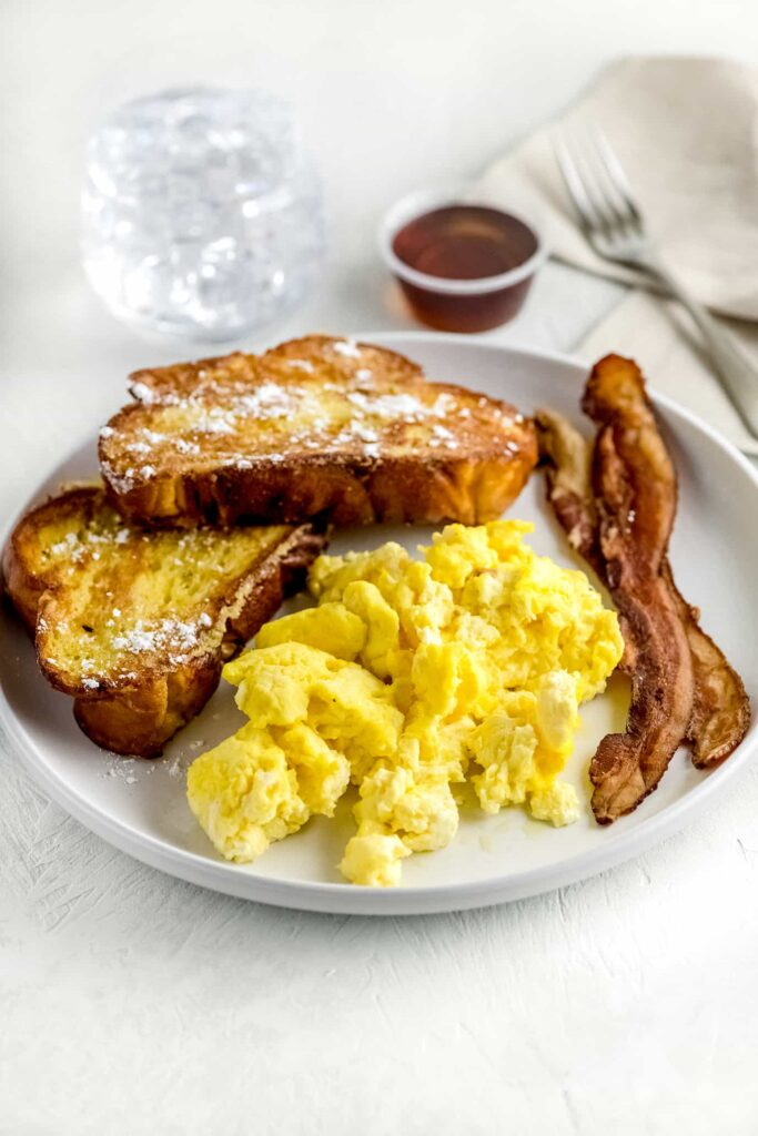 Challah french toast on white plate with scrambled eggs, bacon and syrup