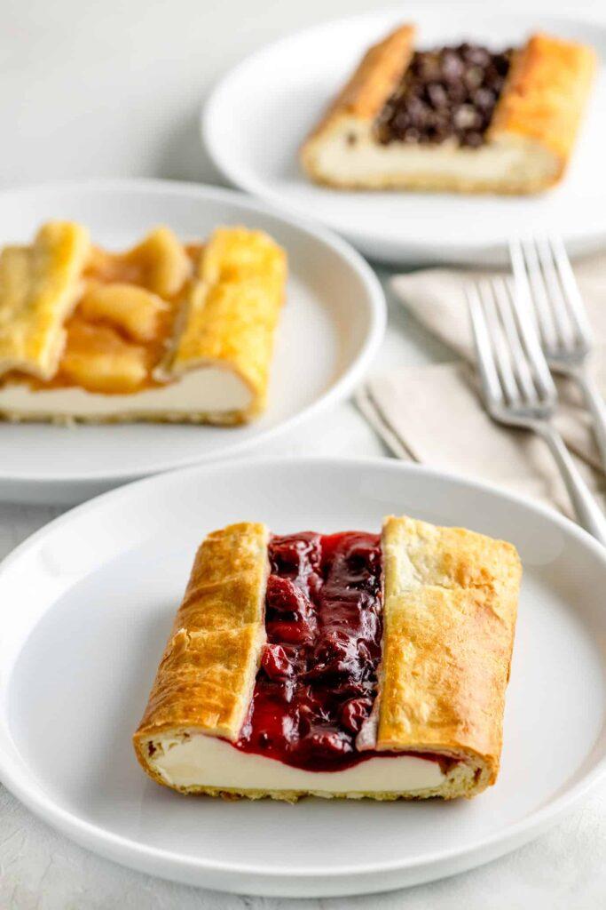 three white plates with a cherry danish, apple cinnamon danish and chocolate cheese danish