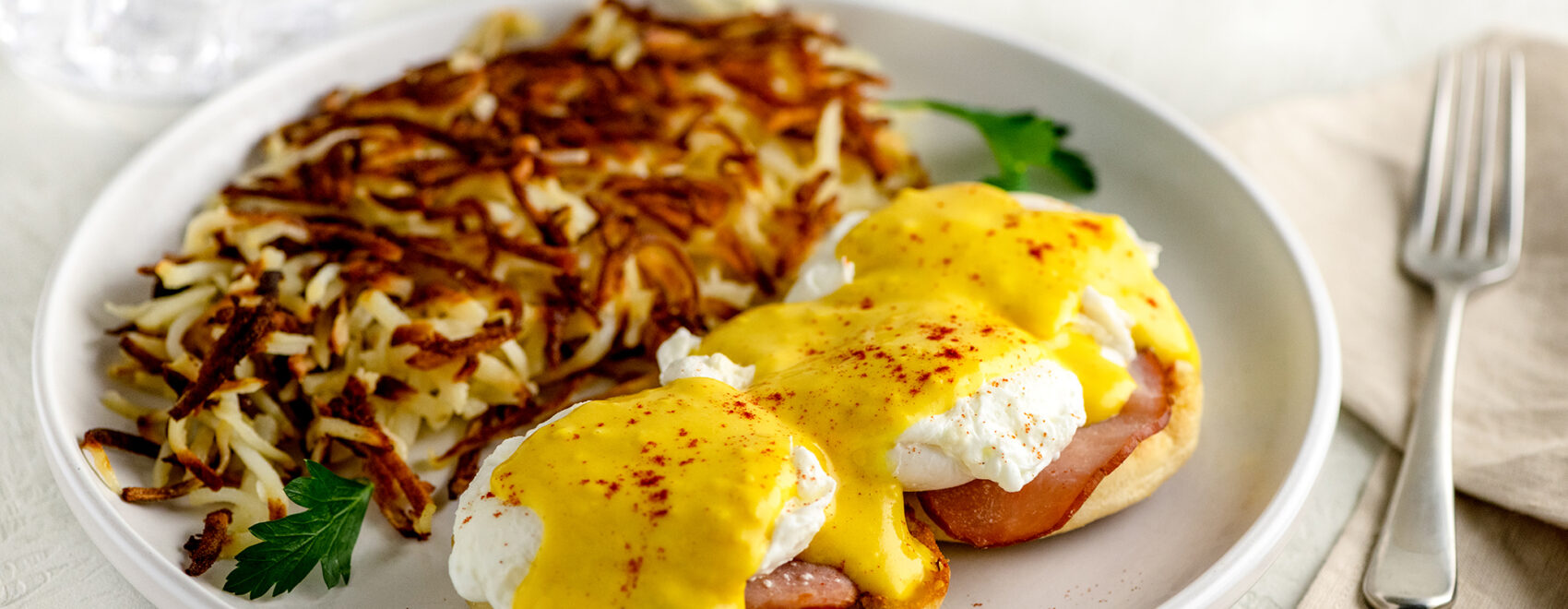 Eggs benedict on white plate with hash browns