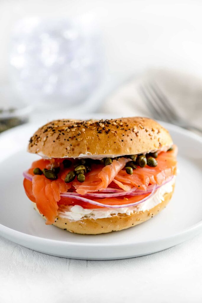 new york bagel with lox, capers and onions on white plate