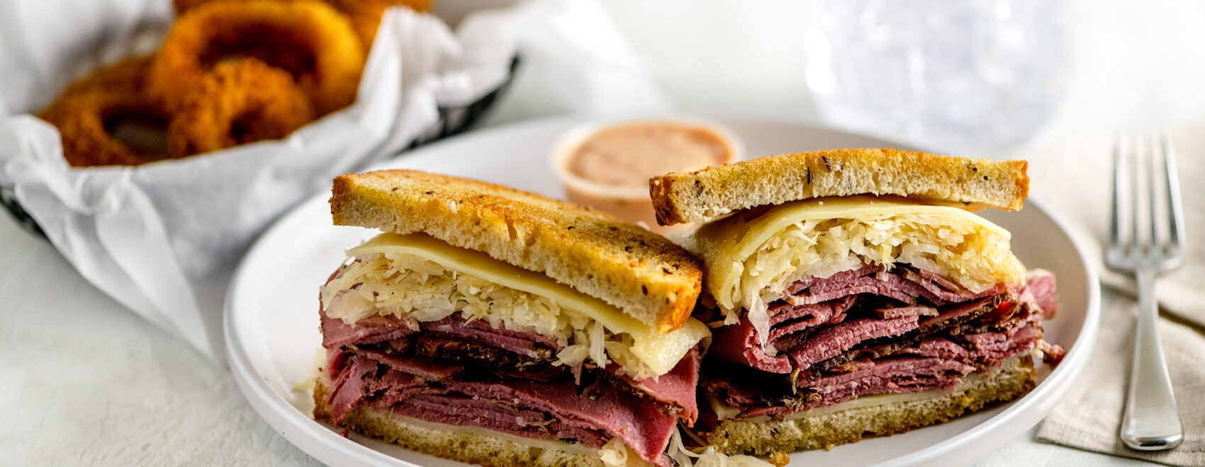 NY pastrami reuben with sauerkraut on rye bread and melted swiss cheese on a white plate. Large order of jumbo crispy onion rings as a side.