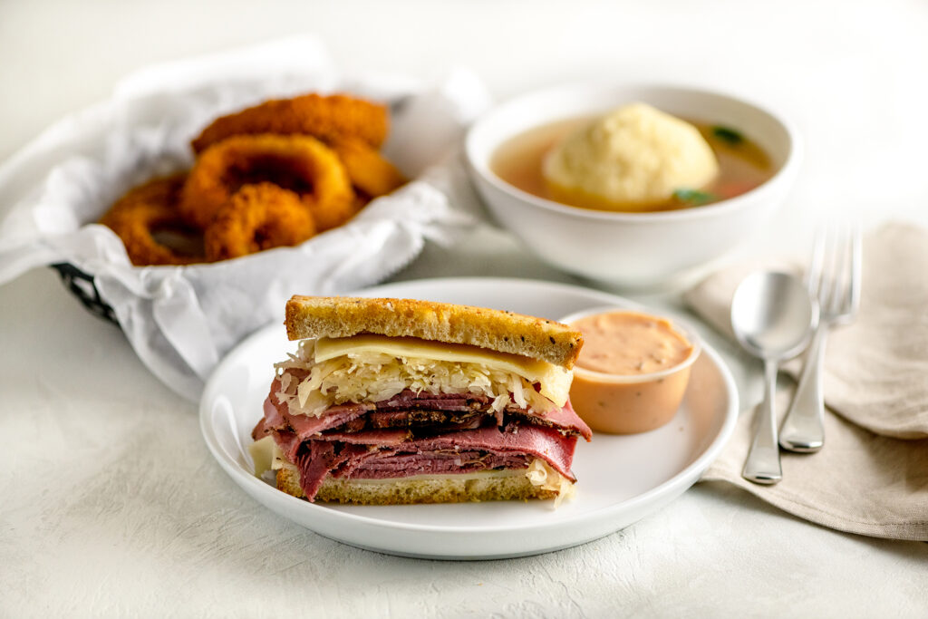 New York Pastrami Reuben on a white plate with onion rings and matzo ball soup
