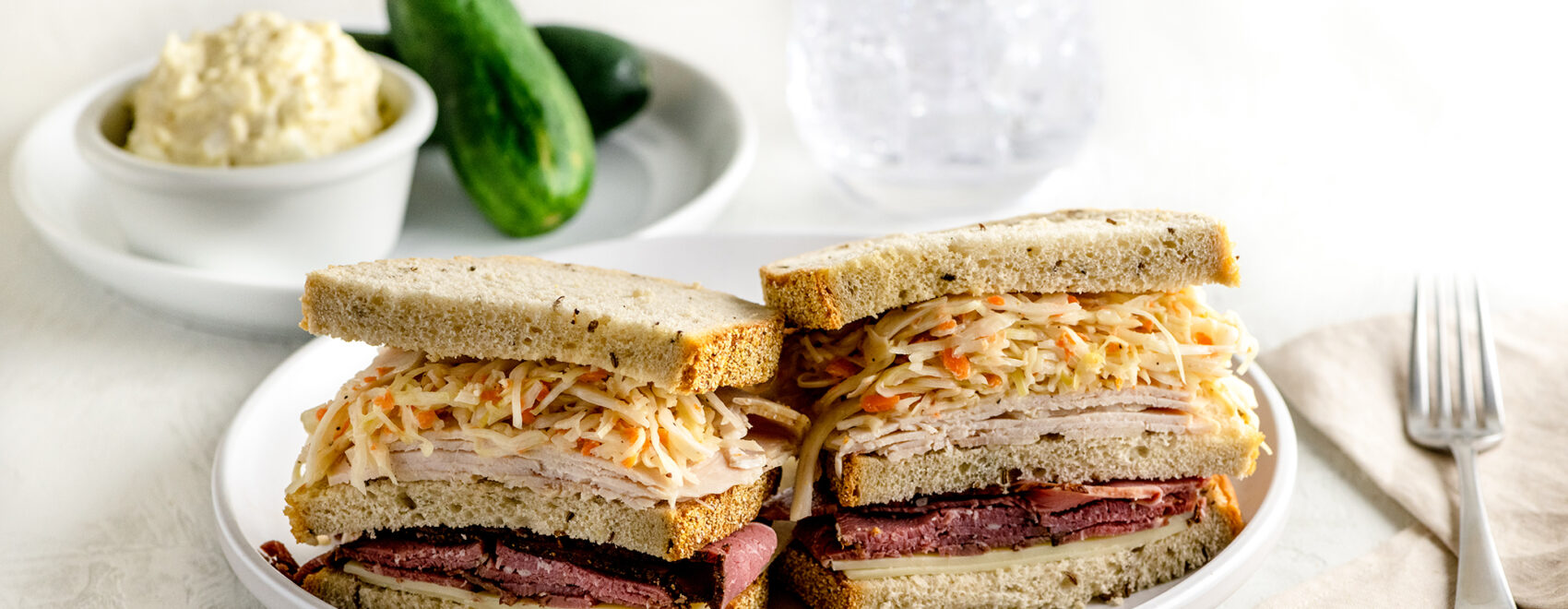triple decker sandwich with pastrami, turkey and cole slaw between 3 slices of rye bread on a white plate. Pickles and potato salad on the side.