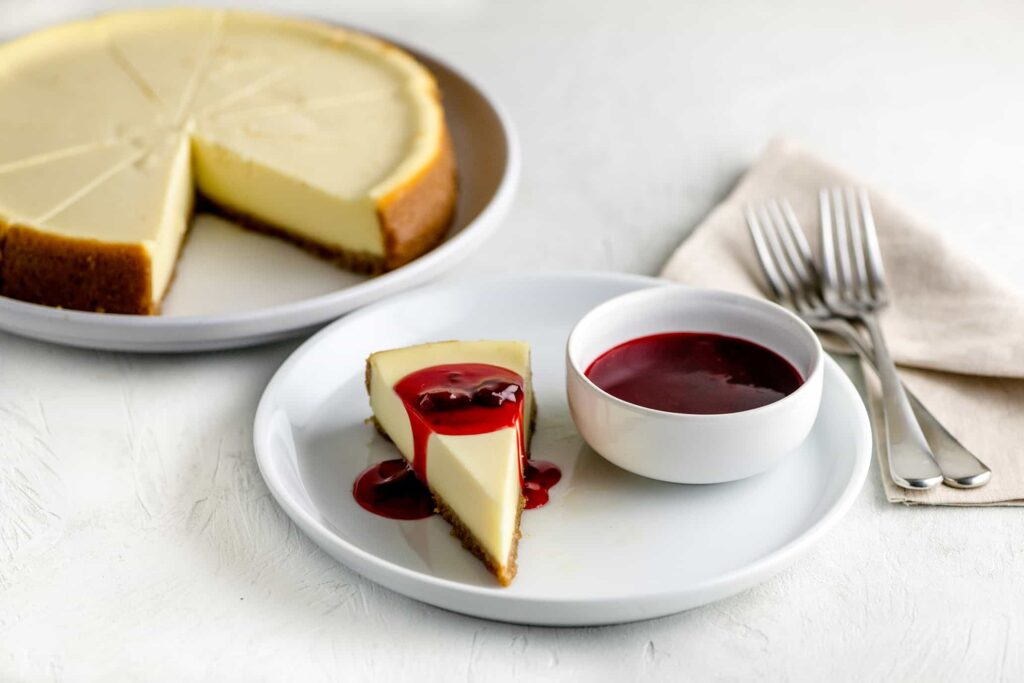 Homemade cheesecake on a white plate beside a small bowl of strawberry topping