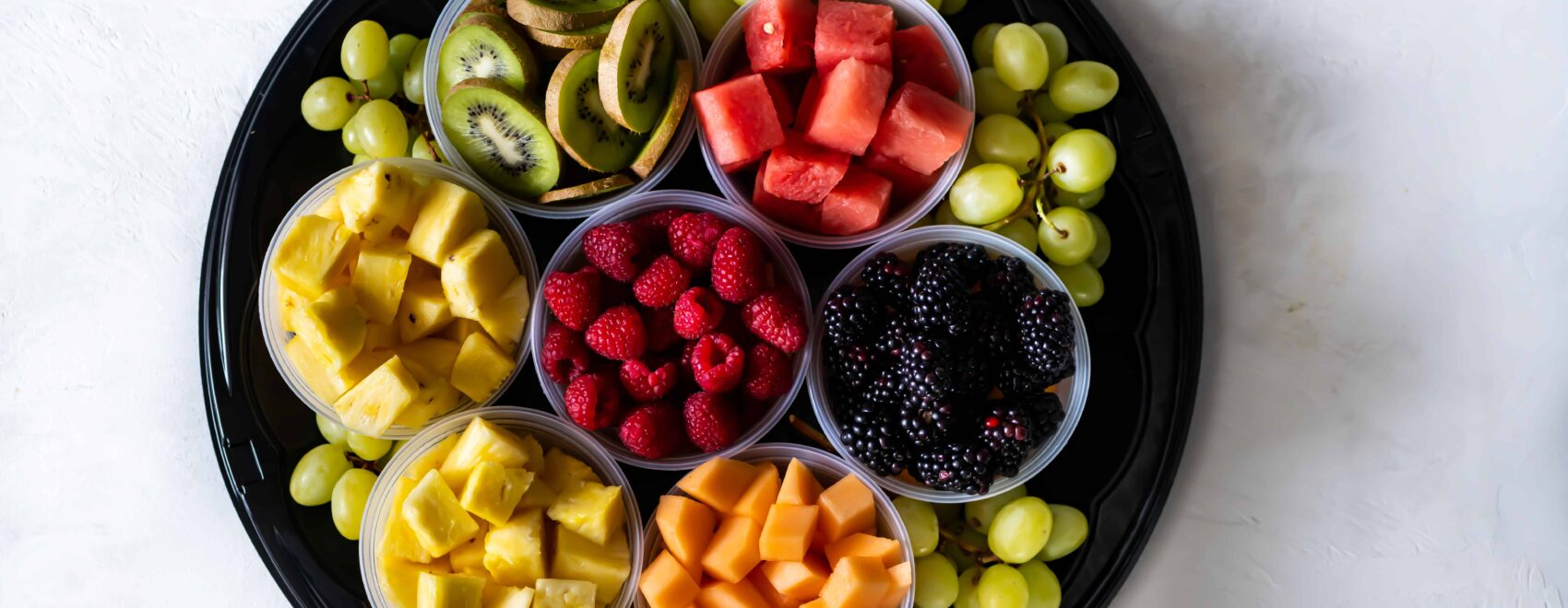 Fruit tray filled with berries, watermelon, grapes, kiwi, melon and pineapple