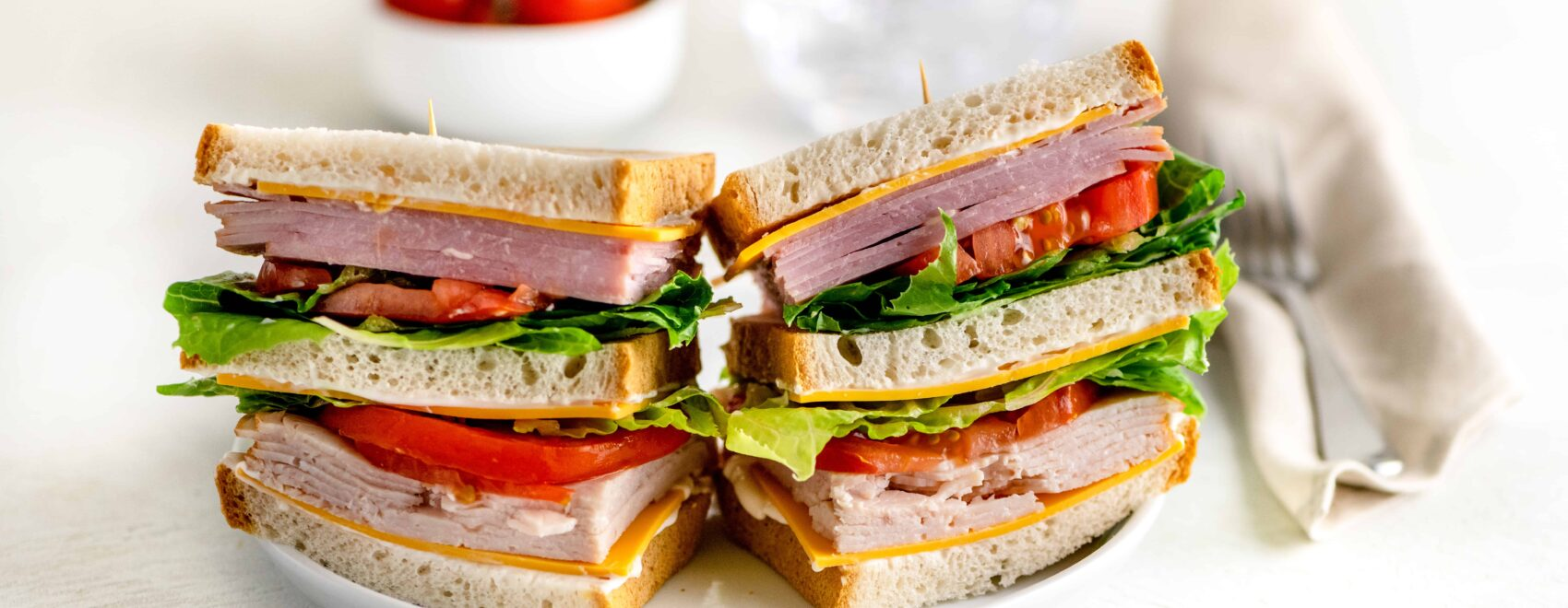 Triple decker sandwich of ham, roasted turkey on three pieces of gluten free bread with cheese, lettuce, tomato and mayo on a white plate