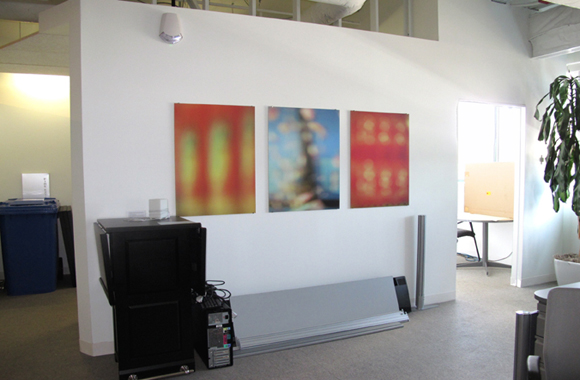 3 abstract photographs hanging on wall of an office