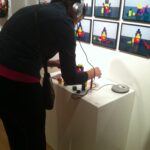 person infront of grid of photographs, building with multicolored blocks